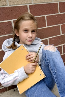 Kid sitting by brick wall
